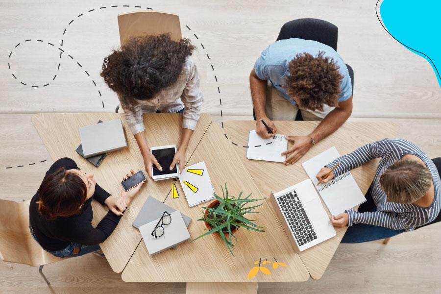 Cuatro colaboradores utilizan sus computadoras, celulares, tabletas y laptops para desarrollar nuevas habilidades con cursos digitales sobre una mesa de madera con una planta.