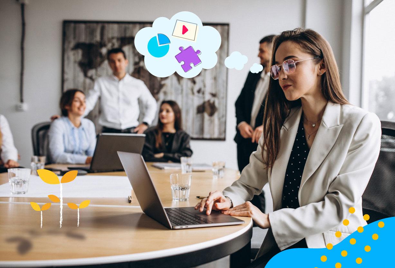 Una mujer adulta con lentes y traje de oficina visualiza un curso de capacitación al personal en la sala de juntas de la empresa.