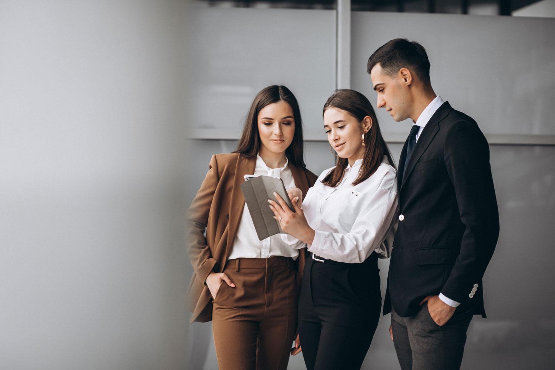 Dos mujeres y un hombre vestidos con ropa de oficina revisan indicadores de la plataforma de capacitación en una tableta mientras trabajan en el corporativo.