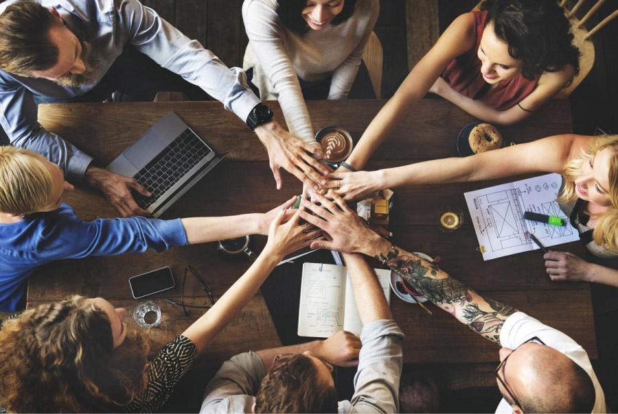 Un grupo de colaboradores en una oficina estrecha sus manos sobre una mesa para la aprobación de un nuevo proyecto mientras se capacitan desde el celular.