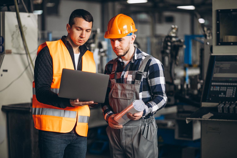 Dos personas, vestidas con casco de protección y chaleco industrial, verifican las actividades y cursos de capacitación que deberán tomar en día en una planta de manufactura.